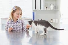 Le den blonda ägaren som daltar hennes kattunge Fotografering för Bildbyråer