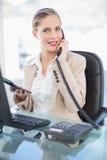 Le den blonda affärskvinnan på den hållande räknemaskinen för telefon Royaltyfri Fotografi