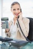 Le den blonda affärskvinnan på telefonvisningräknemaskinen Royaltyfri Bild