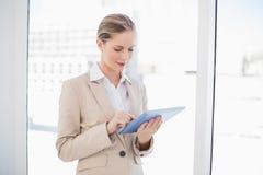 Le den blonda affärskvinnan som använder minnestavlaPC Royaltyfri Fotografi