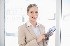 Le den blonda affärskvinnan som använder räknemaskinen Royaltyfri Foto
