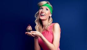 Le den blonda kvinnan med muffin Arkivfoto