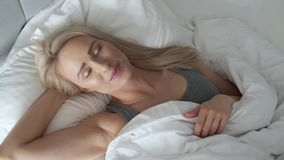 Le den blonda kvinnan som ligger i hennes säng i ljust sovrum under täcket stock video