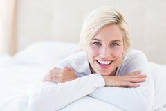 Le den blonda kvinnan som ligger på sängen Royaltyfri Fotografi