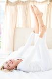 Le den blonda kvinnan som ligger på sängen och att se kameran Royaltyfri Foto