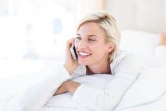 Le den blonda kvinnan som ligger på sängen och kallar på telefonen Royaltyfri Fotografi