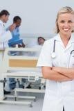 Le den blonda sjuksköterskan som korsar henne armar Royaltyfria Bilder