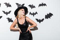 Le den blonda unga kvinnan i häxadräkt med hatten Fotografering för Bildbyråer