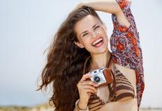 Le den bohemiska unga kvinnan med den retro fotokameran på stranden fotografering för bildbyråer
