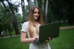 Le den caucasian flickan med bärbara datorn parkera in Lycklig härlig kvinna utan kontorsrutin royaltyfri fotografi