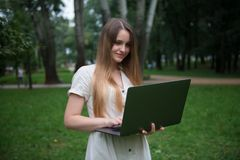 Le den caucasian flickan med bärbara datorn parkera in Lycklig härlig kvinna utan kontorsrutin royaltyfria bilder