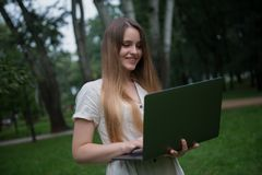 Le den caucasian flickan med bärbara datorn parkera in Lycklig härlig kvinna utan kontorsrutin arkivbild