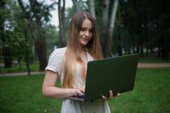 Le den caucasian flickan med bärbara datorn parkera in Lycklig härlig kvinna utan kontorsrutin arkivbilder