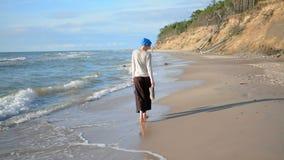 Le den caucasian kvinnan i blå turban som går på stranden som tycker om liv Semestrar begrepp lager videofilmer