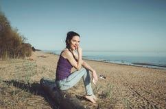 Le den caucasian unga kvinnan i tillfällig jeanskläder som sitter på en träjournal kustfloden Gå för brunettkvinnlig Royaltyfria Foton