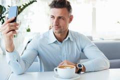 Le den eleganta mogna mannen som bara vilar i kafé med koppen av caf arkivbilder