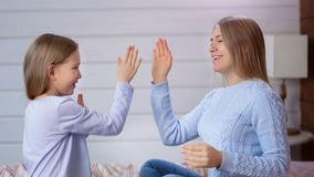 Le den europeiska unga kvinnan och gulliga barnflickan som spelar applådera händer som sitter på säng i sovrum stock video