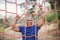 Le den färdiga mannen som klättrar ett netto under hinderkurs royaltyfria bilder
