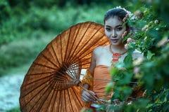 Le den forntida thailändska kvinnan i traditionell dräkt av Thailand Arkivfoton