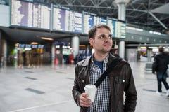 Le den fundersamma mannen framme av ankomster och avvikelser stiga ombord på flygplatsen med ett kaffe royaltyfri bild