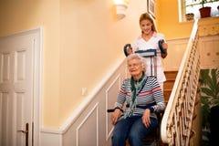 Le den gamla damen som är lycklig, medan sjuksköterskan hjälper henne att klättra till sten royaltyfria foton
