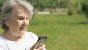 Le den gamla kvinnan talar genom att använda en smart telefon lager videofilmer