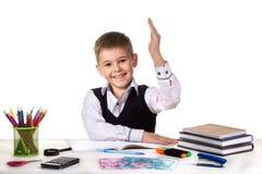Le den gladlynta utmärkta eleven med handen upp sammanträde på tabellen på den vita bakgrunden Royaltyfria Foton