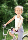 Le den gulliga lilla flickan med hennes cykel Royaltyfri Fotografi