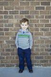 Le den gulliga pojken som är stående upp mot en tegelstenvägg Arkivbilder