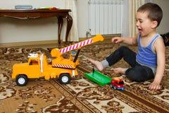 Le den gulliga pysen som spelar med leksaklyftande kranen Royaltyfri Foto