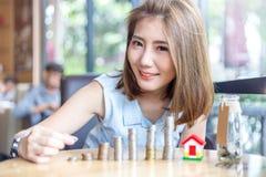 Le den härliga asiatiska kvinnan som staplar guld- mynt royaltyfria foton