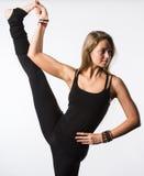Le den härliga flickan i svarta tagande lägga benen på ryggen upp Isolerat på vit Arkivfoto