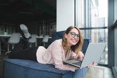 Le den härliga flickan som ligger på en soffa med en bärbar dator i hennes händer på bakgrunden av kontorsdressingen royaltyfri fotografi