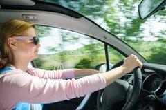 Le den härliga kvinnan i solglasögon som kör bilen på den hög hastigheten Arkivfoton