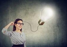 Le den härliga kvinnan som har en idé med den ljusa kulan över hennes huvud arkivbilder