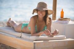 Le den härliga kvinnan som solbadar i en bikini på en strand på det tropiska loppet, tillgripa Arkivfoton