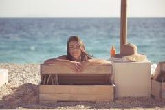 Le den härliga kvinnan som solbadar i en bikini på en strand på det tropiska loppet, tillgripa Arkivfoto