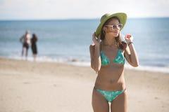 Le den härliga kvinnan som solbadar i en bikini på en strand på det tropiska loppet, tillgripa Fotografering för Bildbyråer