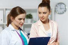 Le den härliga kvinnliga medicindoktorn förklara diagnosen royaltyfria foton