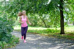 Le den härliga sportiga kvinnan som in joggar, parkera på sommar royaltyfria bilder
