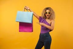 Le den härliga unga kvinnan med påsar Flicka med den afro frisyren och solglasögon Gul bakgrund Till salu begrepp arkivfoto