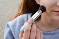 Le den hållande makeupborsten för flicka för att vända mot royaltyfri fotografi