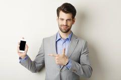 Le den hållande mobilen för ung man i hand Arkivbild