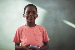 Le den hållande mobiltelefonen för pojke mot greenboard royaltyfria foton