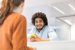 Le den hållande mobiltelefonen för ung affärsman med den kvinnliga kollegan i förgrund på kontoret arkivfoton
