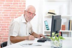 Le den höga affärsmannen med röda exponeringsglas i hans kontor arkivfoto