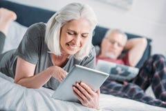 Le den höga kvinnan som använder minnestavlan, medan vila på säng Royaltyfri Fotografi
