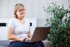 Le den höga kvinnan som hemma arbetar på bärbara datorn royaltyfria bilder