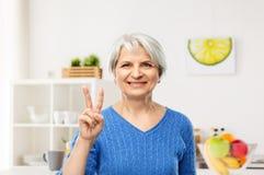 Le den höga kvinnan som visar fred i kök arkivbild