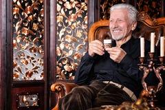 Le den höga mannen som dricker kaffe Royaltyfri Foto
